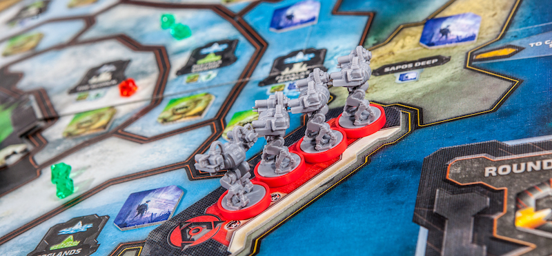 close up of red-based game miniatures set up on game board