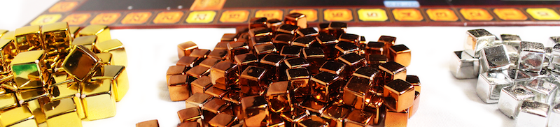 gold, silver, and bronze cube game pieces piled up on game board