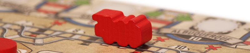 closeup of a red game board piece in the shape of a train, placed upon the game board