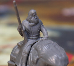 closeup of a game board miniature piece, gray in color; a man holding a shotgun