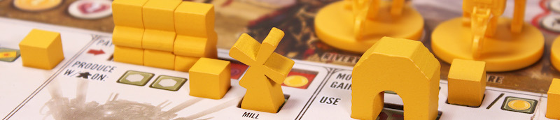 closeup of yellow board game miniatures placed on the game board