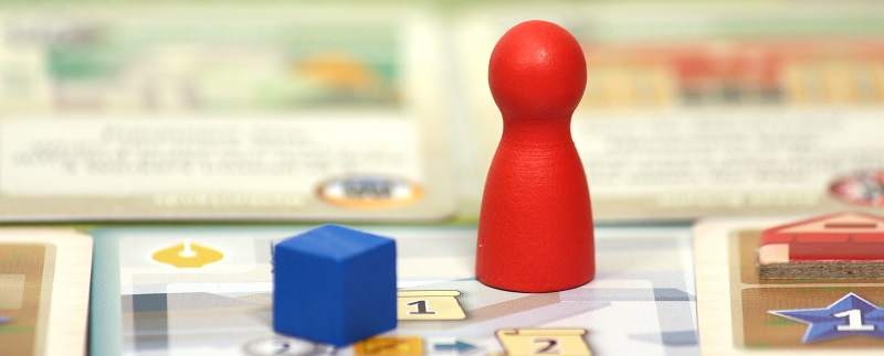 closeup of a red board game miniature placed upon a game board