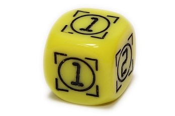 a yellow rounded die, showing three sides with the numbers '1', '1', and '2'