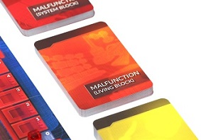 closeup of an orange game card with the words 'Malfunction (Living Block)'