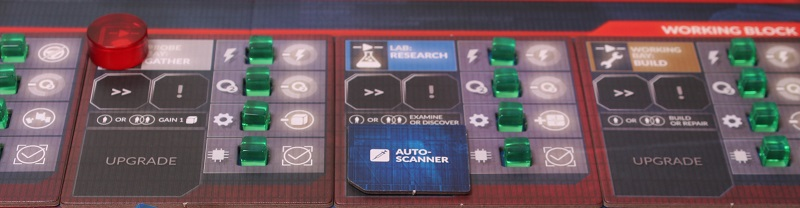 closeup of part of the game board with green cube-shaped pieces, cards, and a red token placed upon the board
