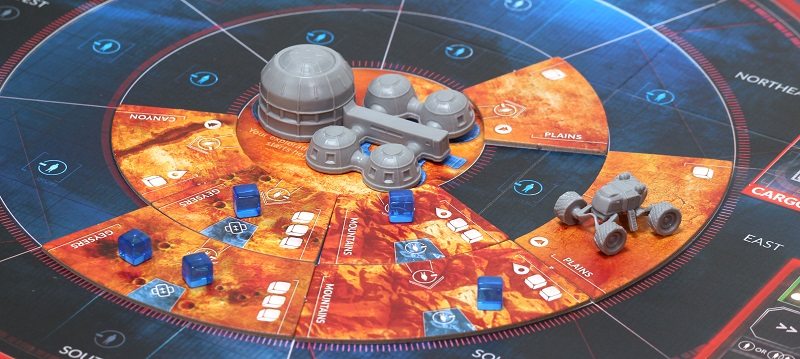 closeup of the orange and blue game board with grey, plastic vehicle miniatures and Mars dwelling miniatures, along with blue cube-shaped game pieces, all placed upon the board