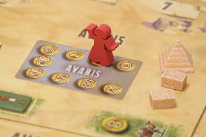 Red wooden meeple on game board with pyramids and stones