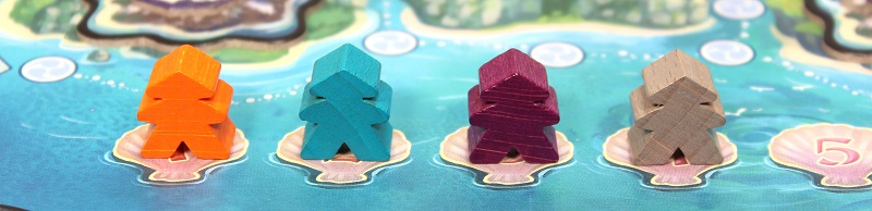 closeup of four board game tokens, resembling meeples with a hat on