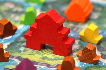 closeup of a red game board piece in the shape of a building