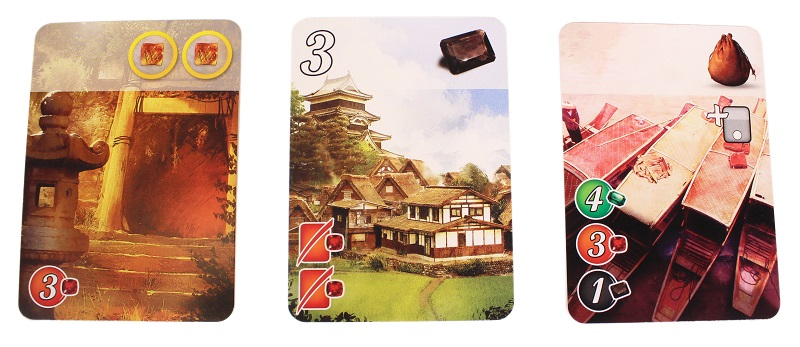 three game cards laid out next to each other, depicting art from the game