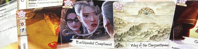 closeup of several cards from the game, including 'Backhanded Compliment', and 'Way of the Chrysanthemum'