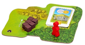 Red meeple and purple wodden cubes on land tile with cards