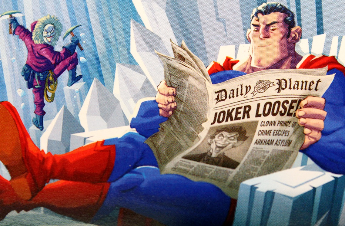 Superman in the Fortress of Solitude reading a newspaper, and The Joker sneaking up on him in the background