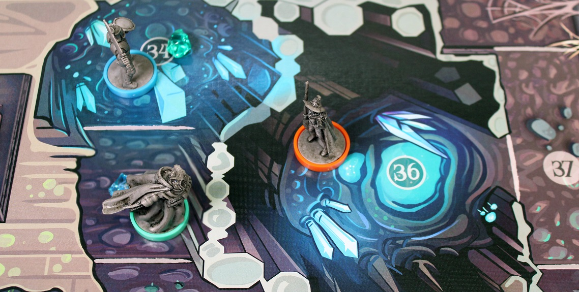closeup of three gray miniatures set up on the game board