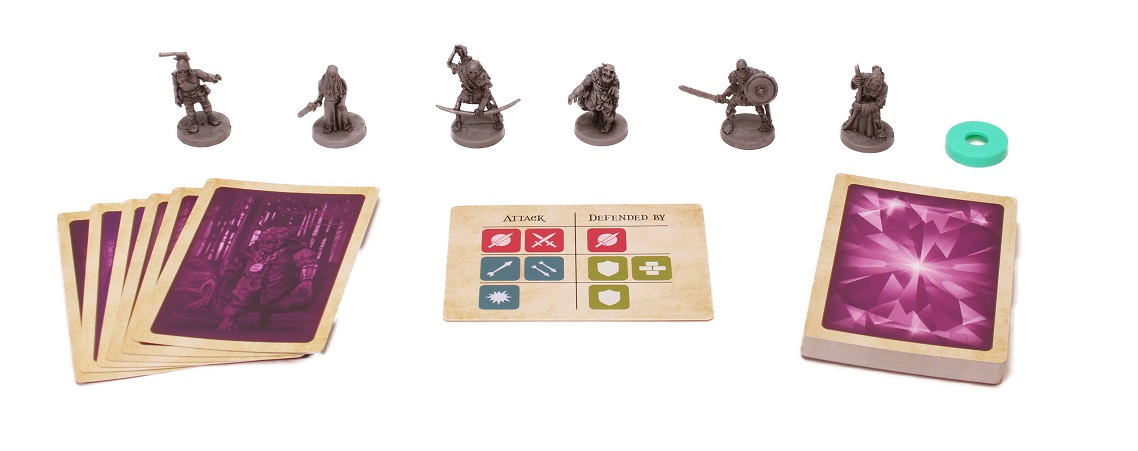 several gray miniatures set up around two stacks of game cards, one token, and one card flipped over to display the words 'attack' and 'defended by'