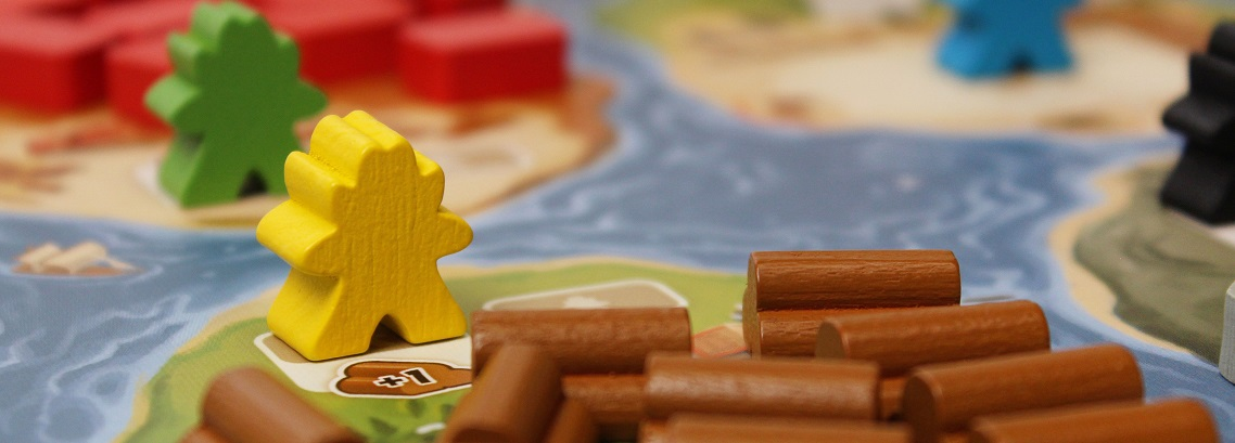 Close-up of multicolored meeples and timber wooden bits on game board