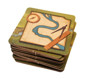 Stack of square punchboard components with map and cartography tools artwork