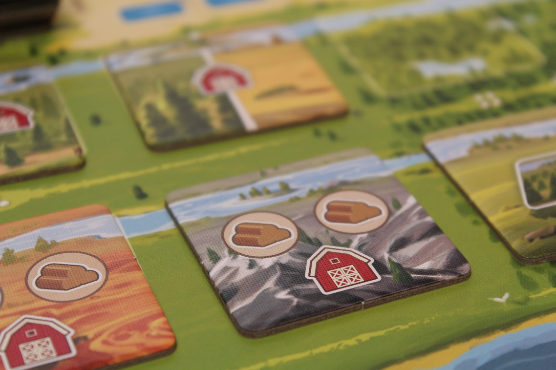 Close-up of game set up with square punchboard components with resource icons