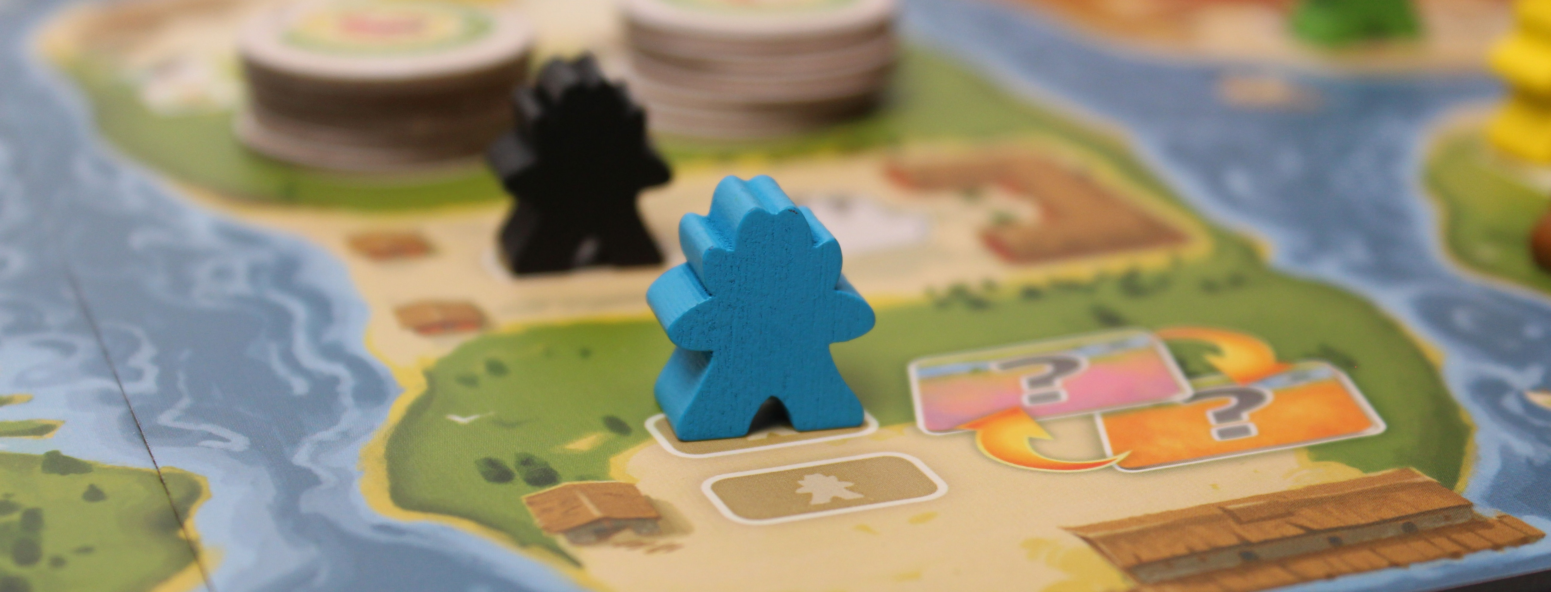 Close-up of game board with river art and multicolored meeples