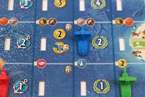 closeup of 7 Wonders: Armada Expansion game board, a green and a blue ship mini game piece are placed on gameboard
